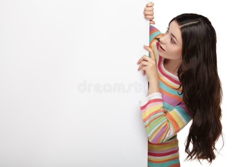 Szczęśliwa uśmiechnięta młoda kobieta pokazuje pustego signboard fotografia royalty free