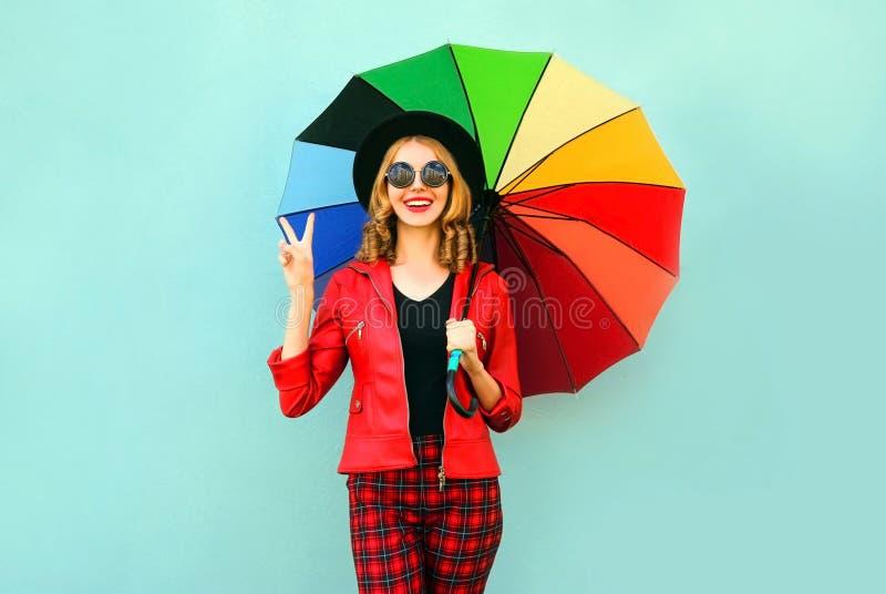 Szczęśliwa uśmiechnięta młoda kobieta trzyma kolorowego parasol w rękach, jest ubranym czerwoną kurtkę, czarny kapelusz na błękit fotografia royalty free
