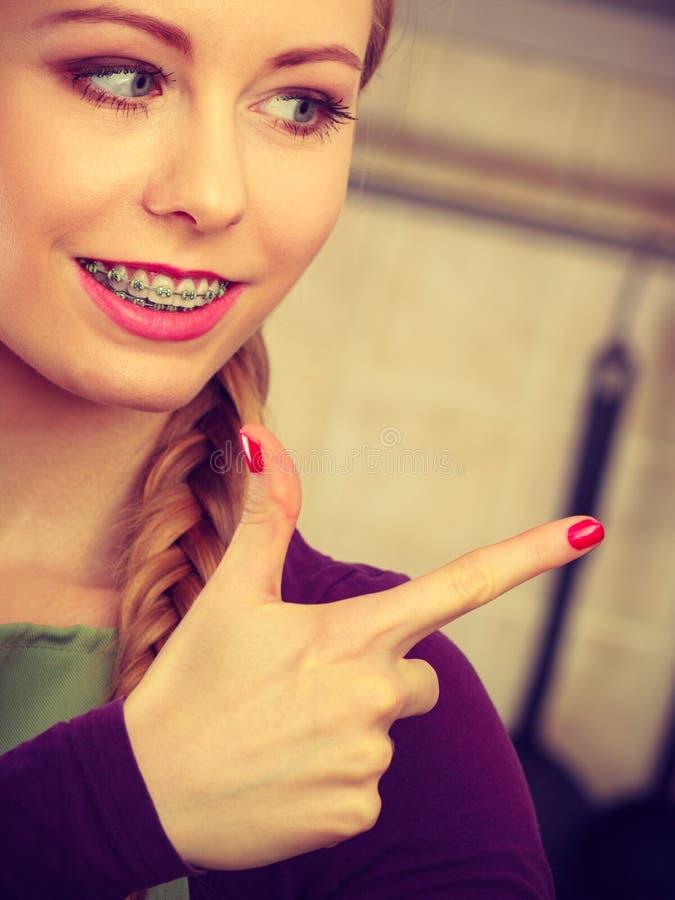 Szczęśliwa uśmiechnięta młoda kobieta z brasów wskazywać zdjęcie stock