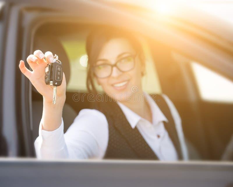 Szczęśliwa uśmiechnięta młoda kobieta z samochodu kluczem obraz royalty free