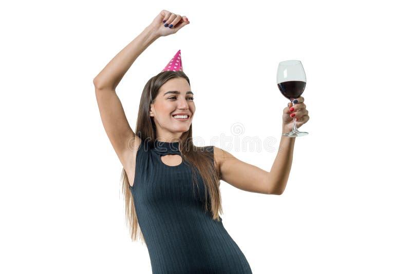 Szczęśliwa uśmiechnięta młoda kobieta z szkłem czerwone wino, w partyjnych kapeluszach, czarna koktajl suknia Na białej odosobnio zdjęcia stock