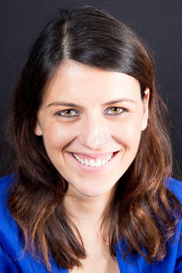 szczęśliwa uśmiechnięta młoda piękna kobieta w błękitnej przypadkowej odzieży nad czarnym tłem, obrazy stock