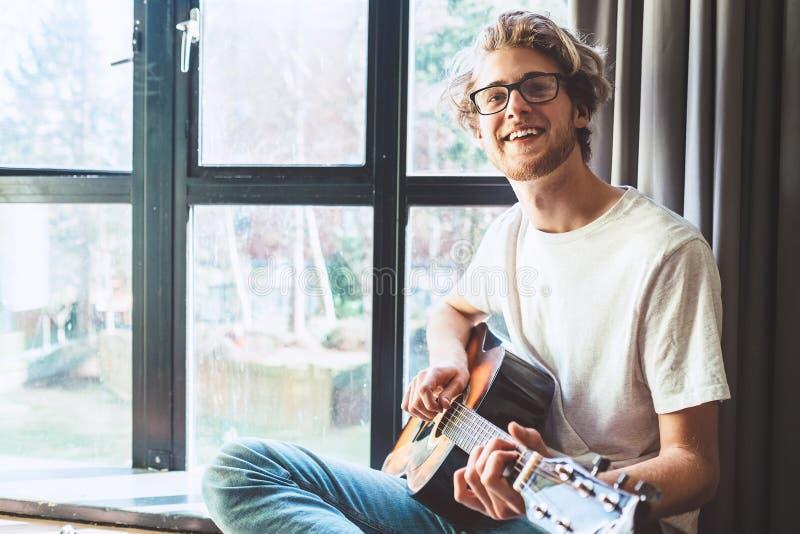 Szczęśliwa uśmiechnięta młody człowiek sztuka na gitarze blisko okno obraz royalty free