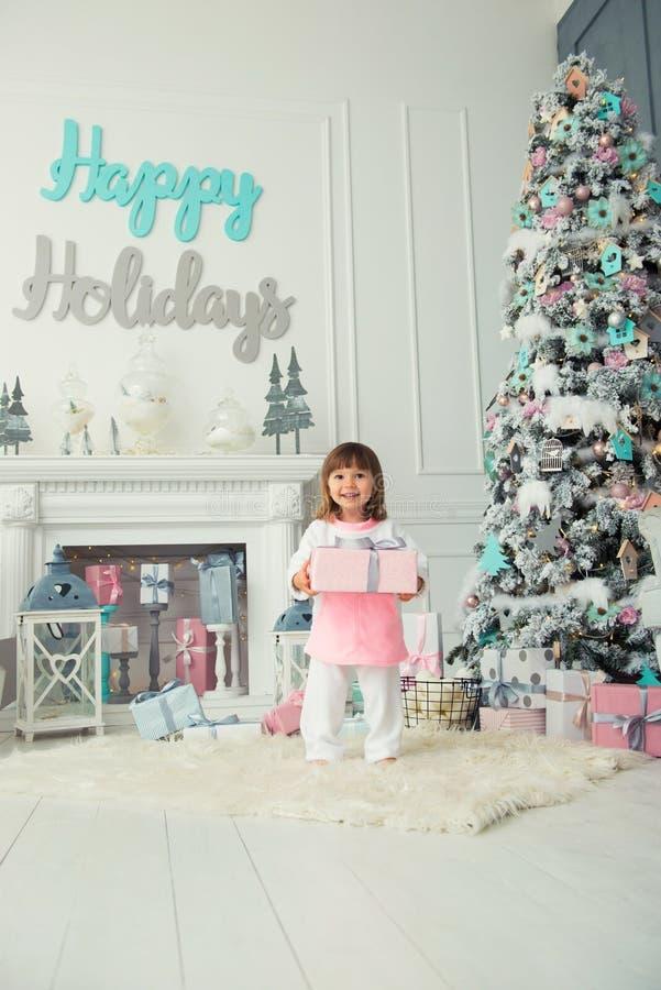 Szczęśliwa uśmiechnięta mała dziewczynka stoi z Bożenarodzeniowymi teraźniejszość blisko nowego roku drzewa Wakacje 2018 i prezen obrazy royalty free