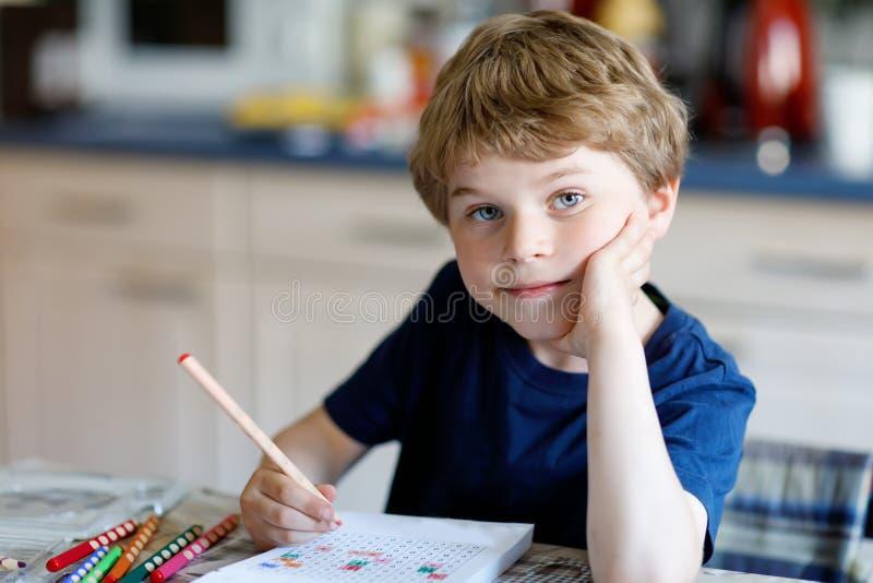 Szczęśliwa uśmiechnięta małe dziecko chłopiec robi pracie domowej przy rankiem przed szkolnymi początkami w domu Małego dziecka r obrazy royalty free