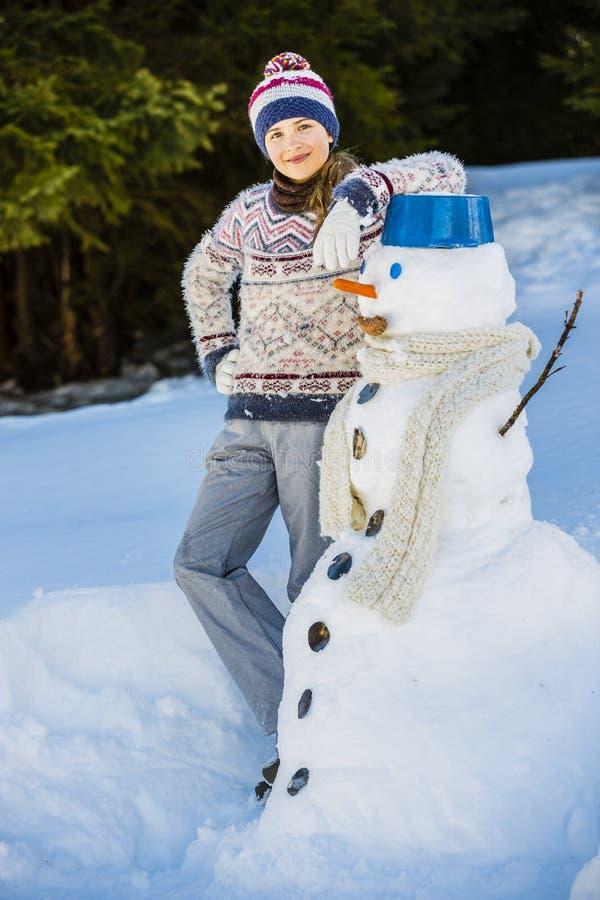Szczęśliwa uśmiechnięta nastoletnia dziewczyna bawić się z bałwanem na śnieżnej wygranie obraz stock
