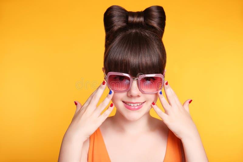 Szczęśliwa uśmiechnięta nastoletnia dziewczyna z moda okularami przeciwsłonecznymi, łęk fryzura a zdjęcia royalty free