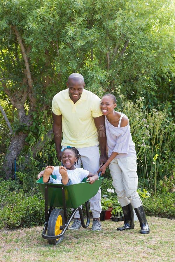 Szczęśliwa uśmiechnięta para bawić się z wheelbarrow i ich synem zdjęcie royalty free