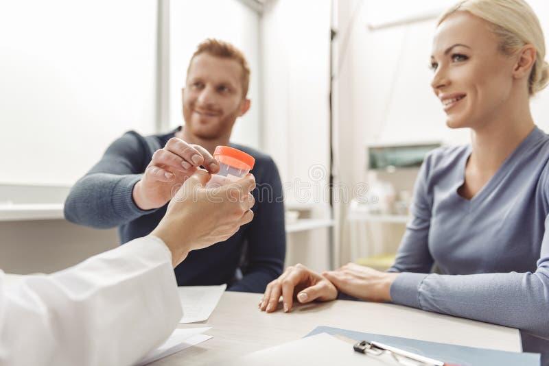 Szczęśliwa uśmiechnięta para odwiedza lekarkę obrazy royalty free