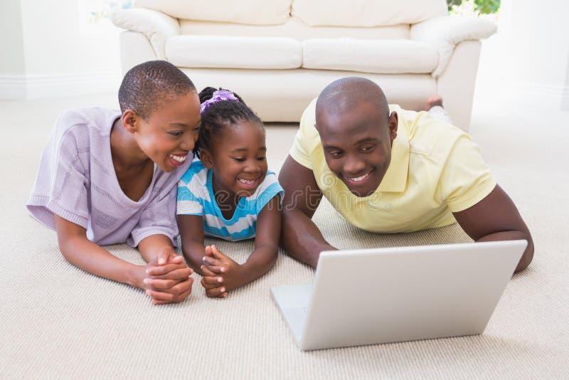 Szczęśliwa uśmiechnięta para używa laptop z ich córką obrazy stock