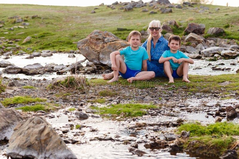 Szczęśliwa uśmiechnięta pięćdziesięcioletnia kobieta i dwa rozochoconego wnuka siedzi na zielonej trawie obraz royalty free