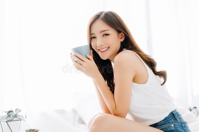 Szczęśliwa uśmiechnięta piękna Azjatycka kobieta budzi z filiżanka kawy i patrzeje kamerę w sypialni Gnu?ny dnia wolnego poj?cie zdjęcia stock