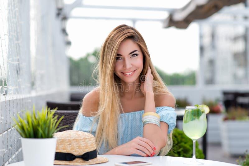 Szczęśliwa uśmiechnięta piękna dziewczyna z długie włosy Kobieta w lato kawiarni na werandzie restauracja Siedzi przy stołem w a zdjęcie stock