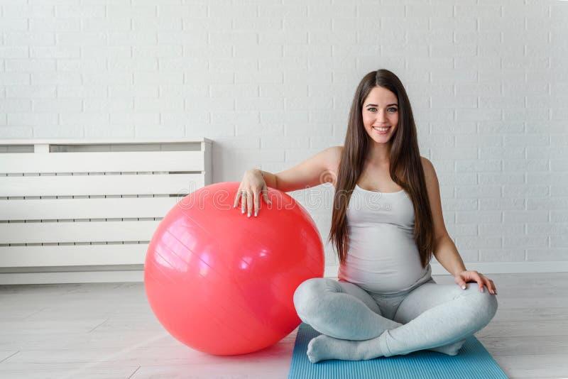 Szczęśliwa uśmiechnięta piękna kobieta w ciąży ćwiczy w domu z pilates balowymi obraz stock