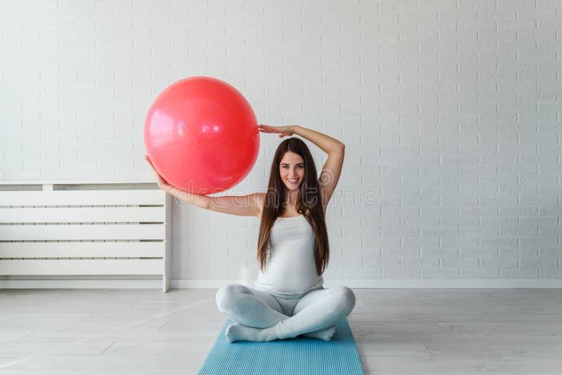 Szczęśliwa uśmiechnięta piękna kobieta w ciąży ćwiczy w domu z pilates balowymi obrazy stock