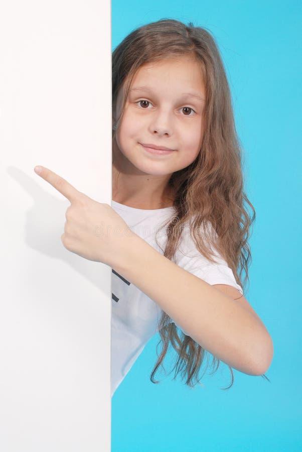 Szczęśliwa uśmiechnięta piękna młoda dziewczyna pokazuje pustego signboard lub copyspace dla sloganu lub teksta obraz stock