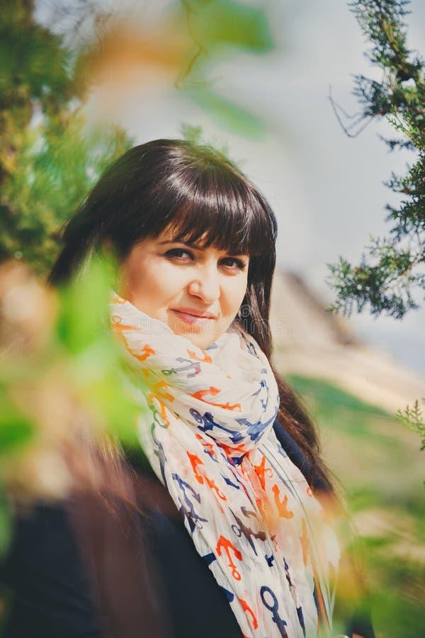 Szczęśliwa uśmiechnięta piękna z nadwagą młoda kobieta w zmroku - niebieska marynarka i szalik z kotwicą outdoors Ufna gruba młod zdjęcie stock