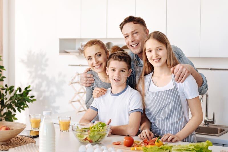 Szczęśliwa uśmiechnięta rodzinna pozycja w kuchni wpólnie zdjęcie royalty free