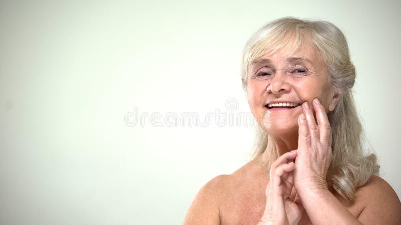 Szczęśliwa uśmiechnięta stara żeńska macanie twarz, stosuje starzenie się śmietankę, kosmetologia zdjęcia royalty free