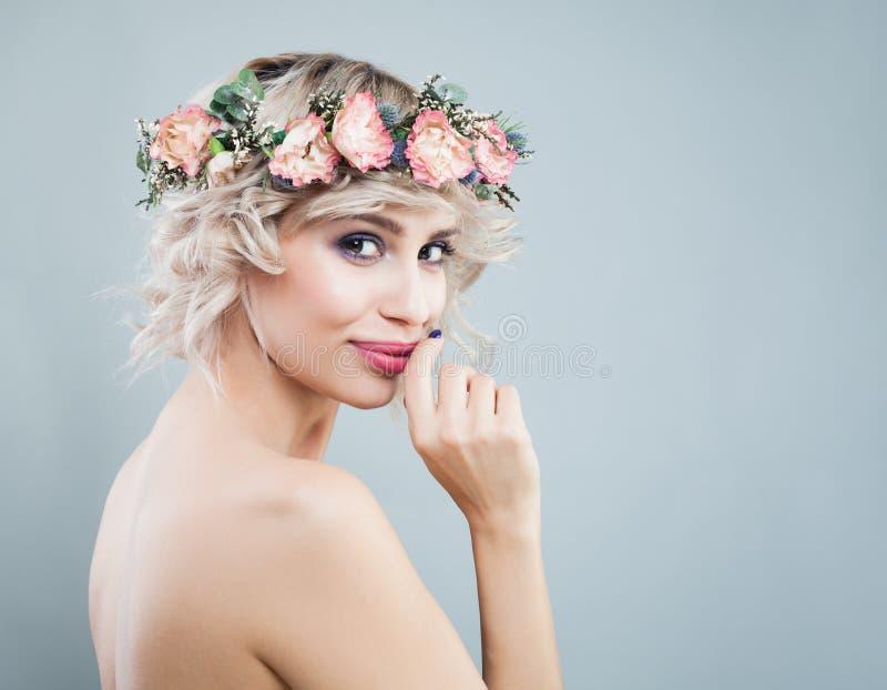 Szczęśliwa uśmiechnięta wzorcowa kobieta jest ubranym kwiat koronę Kędzierzawy włosy, Makeup i kwiaty, obraz stock