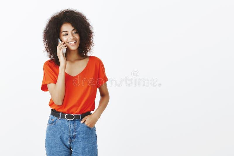 Szczęśliwa ufna i atrakcyjna garbnikująca kobieta z afro ostrzyżeniem, trzymający rękę w kieszeni i smartphone blisko ucho, patrz zdjęcie stock