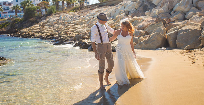 Szczęśliwa właśnie zamężna młoda ślub pary odświętność i zabawę przy piękną plażą obrazy royalty free