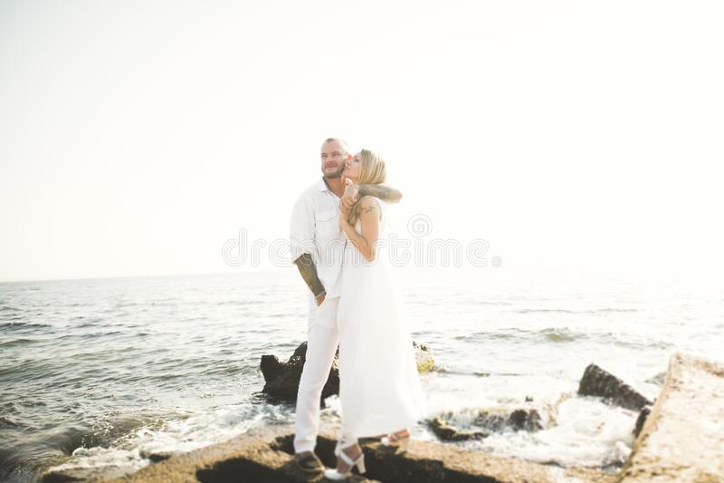 Szczęśliwa właśnie zamężna młoda ślub pary odświętność i zabawę przy pięknym plażowym zmierzchem fotografia royalty free