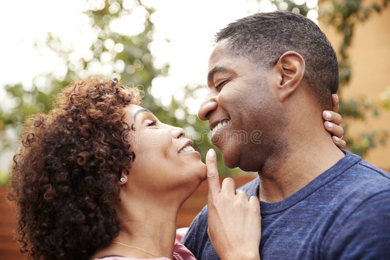 Szczęśliwa w średnim wieku amerykanin afrykańskiego pochodzenia para obejmuje outdoors, boczny widok, zakończenie w górę obraz stock