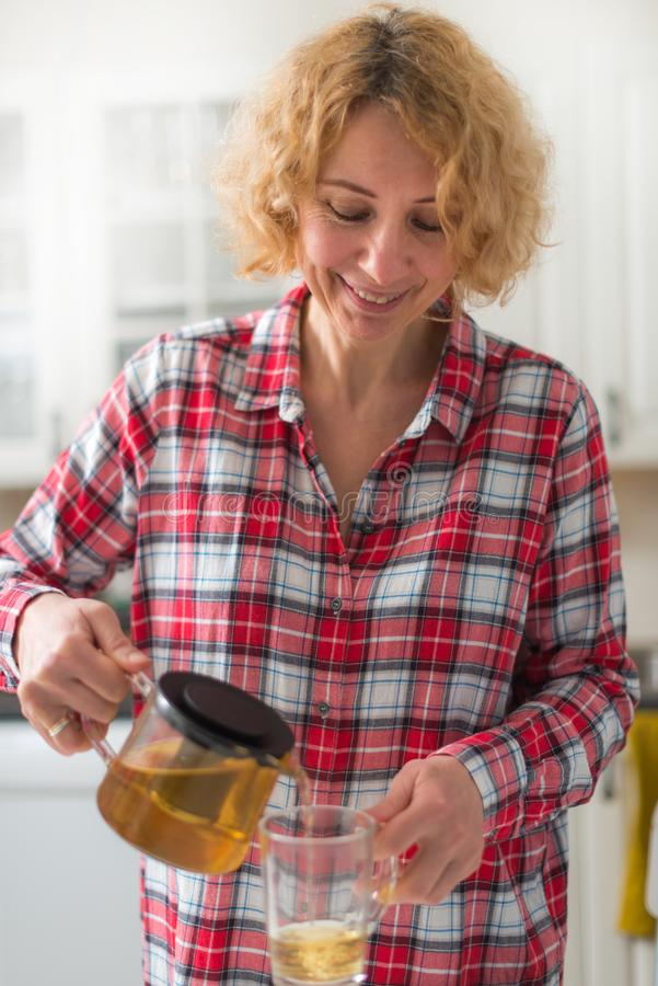 Szczęśliwa w średnim wieku kobiety dolewania herbata zdjęcia royalty free