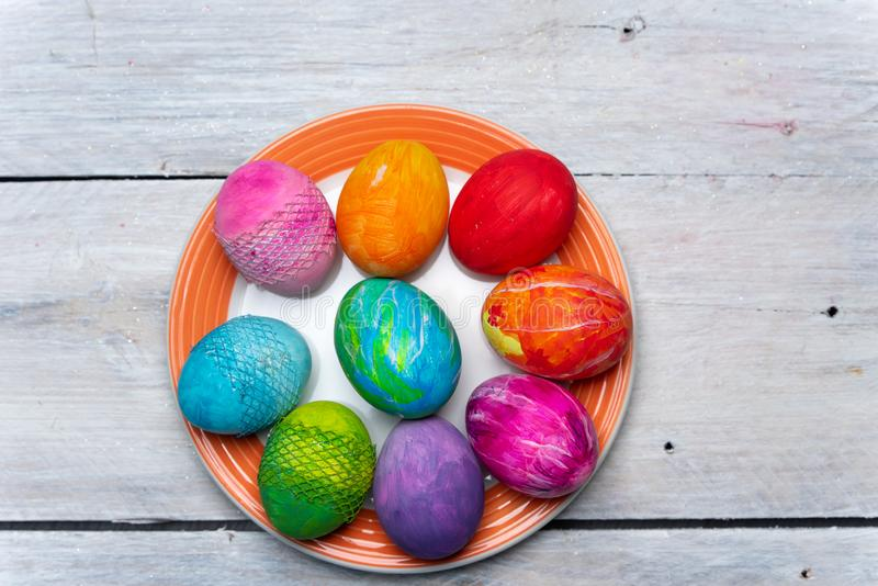 Szczęśliwa wielkanoc - odgórny widok na talerzu z barwiącymi jajkami na drewnianym lekkim tle zdjęcie royalty free