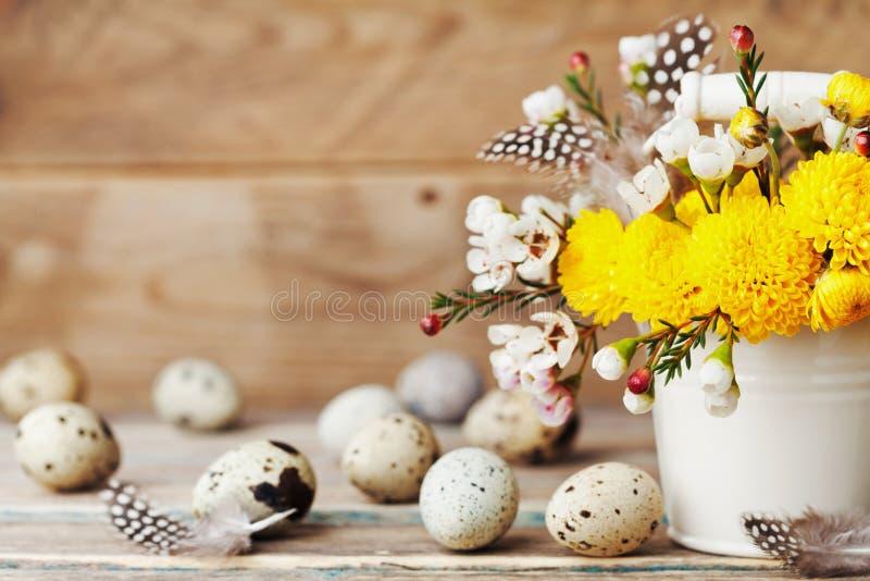 Szczęśliwa Wielkanocna karta z kolorowymi kwiatami, piórkiem i przepiórek jajkami na rocznika drewnianym tle, Piękny wiosna skład zdjęcia stock