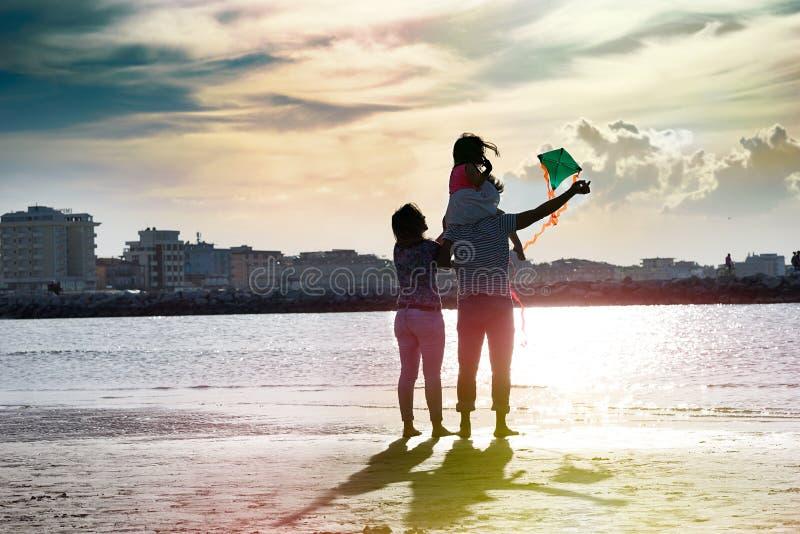 Szczęśliwa wielokulturowa rodzina z małą śliczną dziewczyną na plażowy cieszyć się latający kanię zdjęcie stock