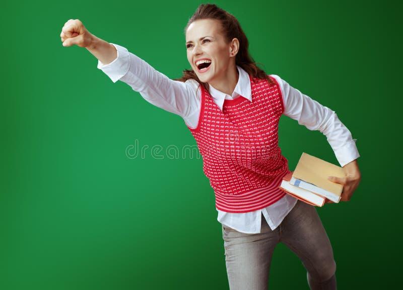 Szczęśliwa współczesna uczennica z książkami latającymi jak superbohater obrazy stock