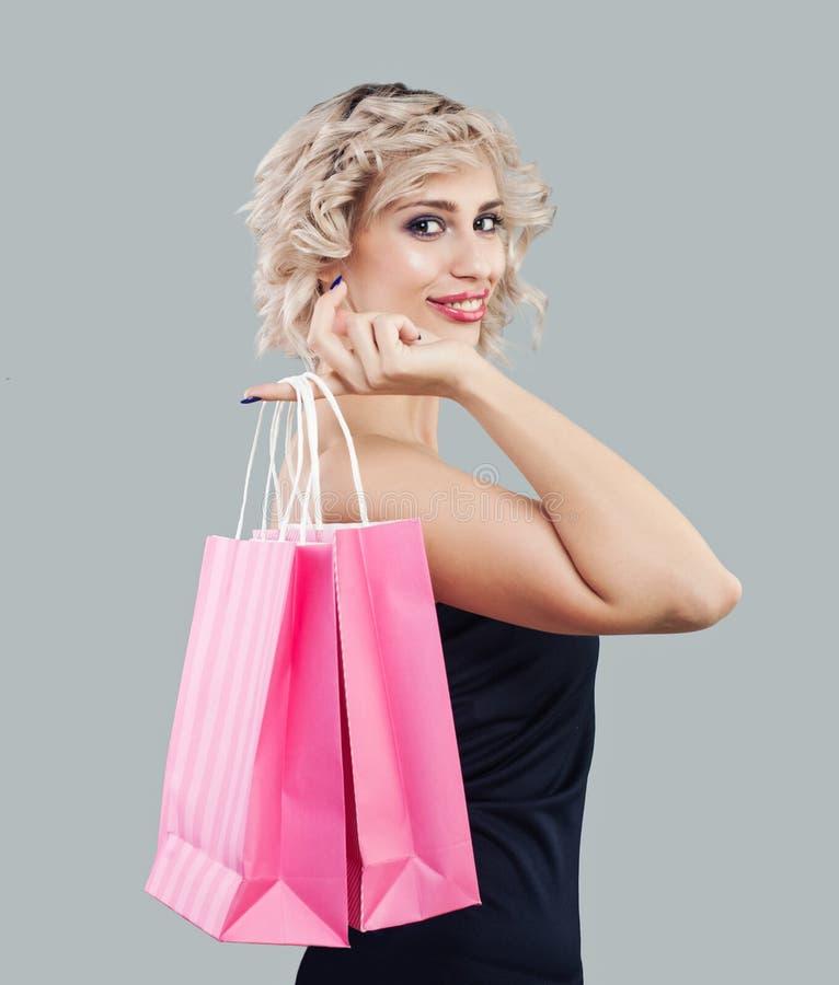 Szczęśliwa wzorcowa kobiety mienia menchii torba na zakupy obrazy stock