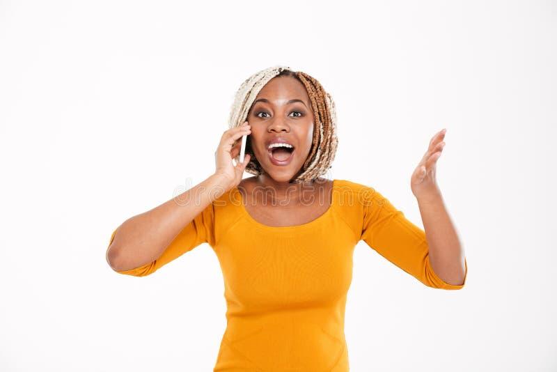 Szczęśliwa z podnieceniem amerykanin afrykańskiego pochodzenia kobieta opowiada na telefonie komórkowym obrazy stock