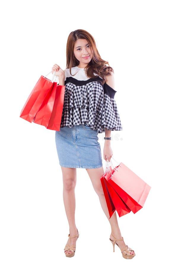 Szczęśliwa z podnieceniem kobiety pozycja i mień kolorowi torba na zakupy odizolowywający obrazy stock