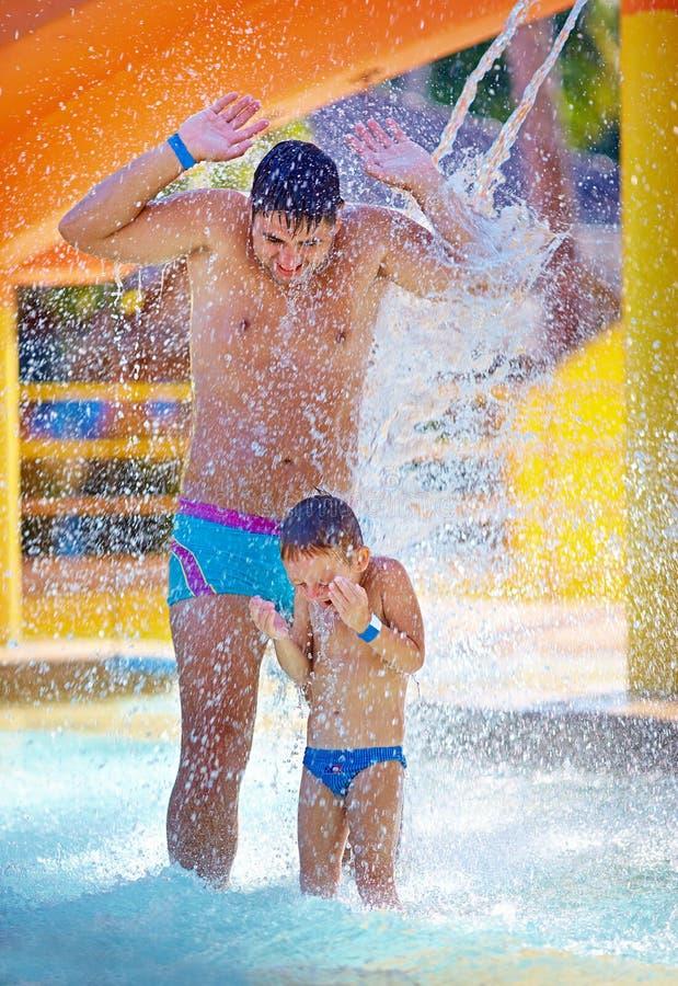 Szczęśliwa z podnieceniem rodzina pod wodnym strumieniem w woda parku fotografia stock