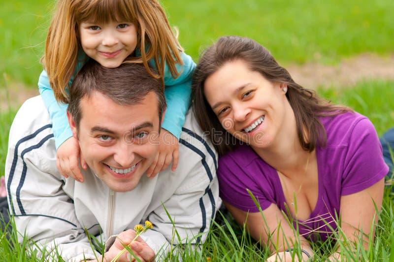 szczęśliwa zabawy rodzinna trawa mieć potomstwo zdjęcie royalty free