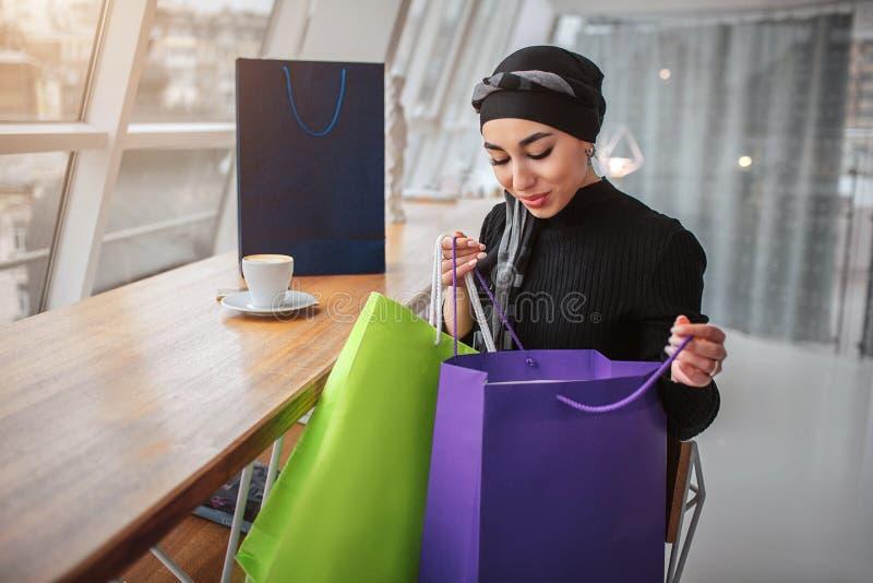 Szczęśliwa zadowolona arabska kobieta siedzi wśrodku Trzyma torby na zakupy i spojrzenie wśrodku one Wzorcowa odzieży czerni sukn zdjęcie royalty free