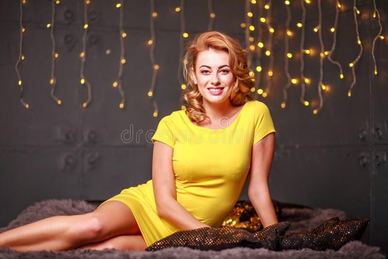 Szczęśliwa zadumana młoda kobieta na kanap świateł świątecznym tle zdjęcie stock