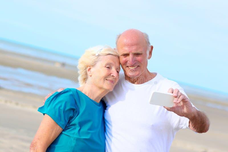 Szczęśliwa zdrowa przechodzić na emeryturę starszej osoby para cieszy się wakacje na plaży obrazy stock