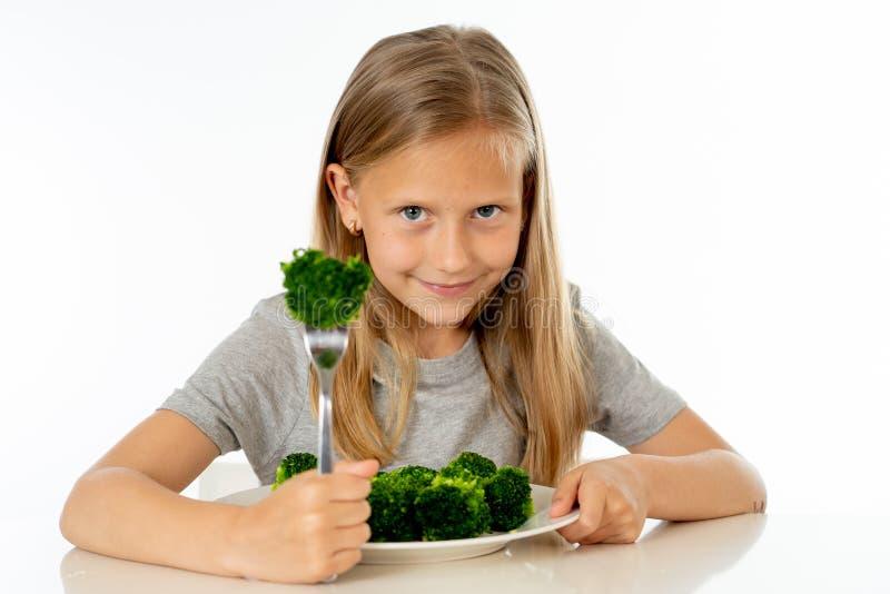 Szczęśliwa zdrowa Yong dziewczyna je jej brokułów warzywa w zdrowym łasowania pojęciu fotografia stock