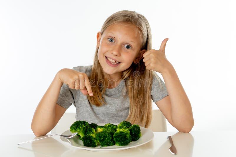 Szczęśliwa zdrowa Yong dziewczyna je jej brokułów warzywa w zdrowym łasowania pojęciu zdjęcia stock