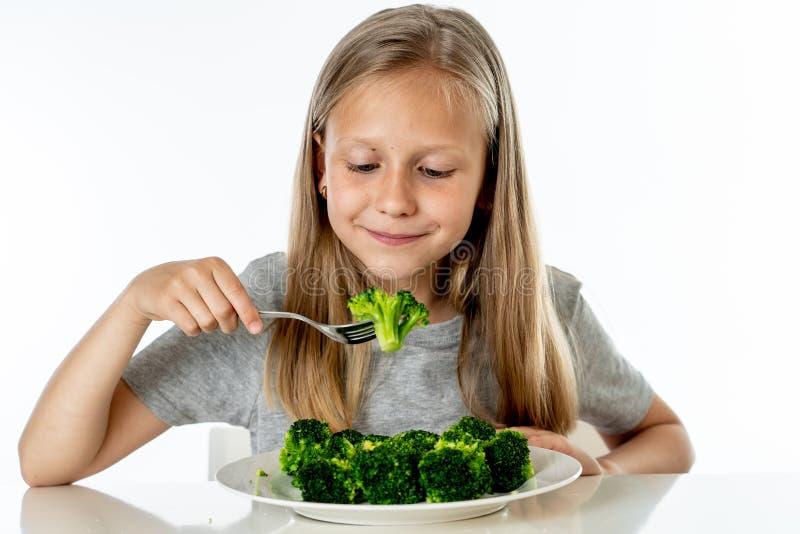 Szczęśliwa zdrowa Yong dziewczyna je jej brokułów warzywa w zdrowym łasowania pojęciu zdjęcie royalty free