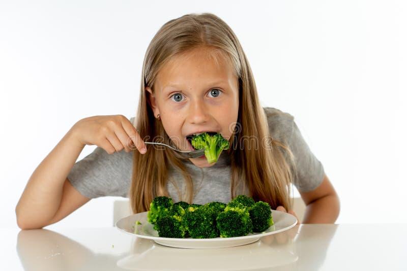 Szczęśliwa zdrowa Yong dziewczyna je jej brokułów warzywa w zdrowym łasowania pojęciu obraz royalty free