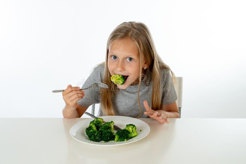 Szczęśliwa zdrowa Yong dziewczyna je jej brokułów warzywa w zdrowym łasowania pojęciu zdjęcia royalty free