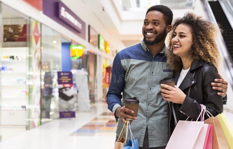 Szczęśliwe afrykańskie pary mienia torby na zakupy i patrzeć na gablotę wystawową obraz royalty free