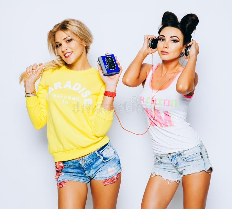 Szczęśliwe atrakcyjne dziewczyny słucha muzyka od starego kaseta gracza i ma zabawę w lato stroju zdjęcie stock