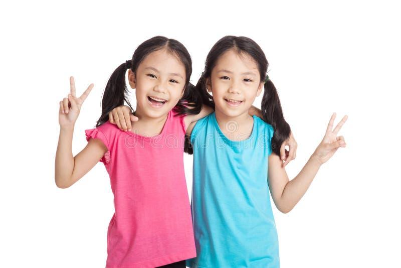 Szczęśliwe Azjatyckie bliźniak dziewczyny uśmiechają się przedstawienia zwycięstwa znaka obraz stock