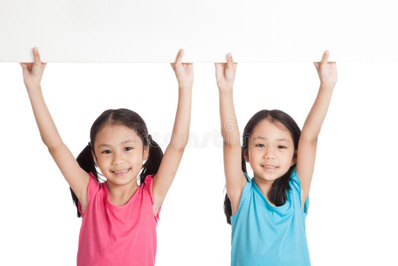 Szczęśliwe Azjatyckie bliźniak dziewczyny z białym pustym sztandaru koszt stały obraz royalty free
